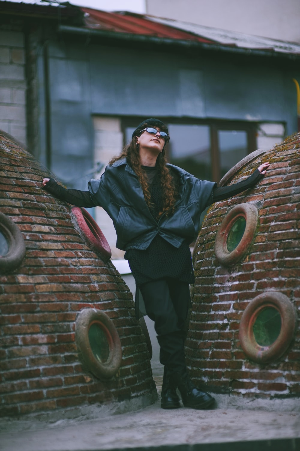woman standing between red brick walls