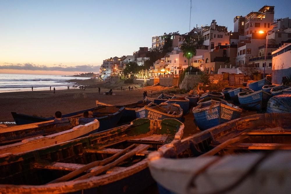 boats on seashore near houses