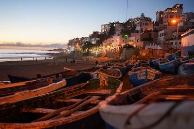 boats on seashore near houses morocco zoom background