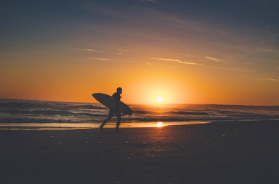 silhouette of person holding surfboard near body of water surfing teams background