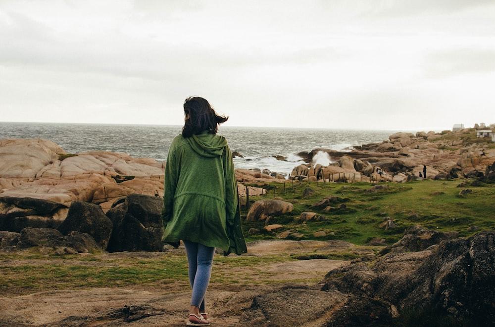 woman walking near rocky shore