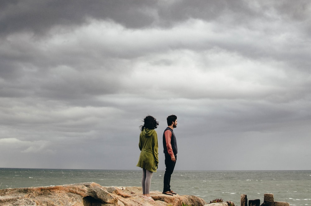 man and woman standing on cliff near sea