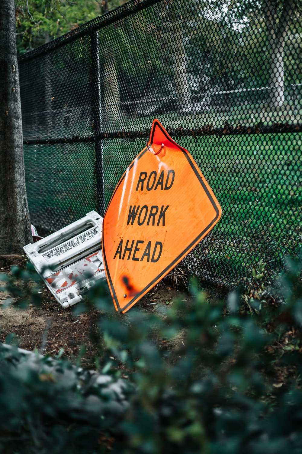 road work ahead signage leaning on chain link fence