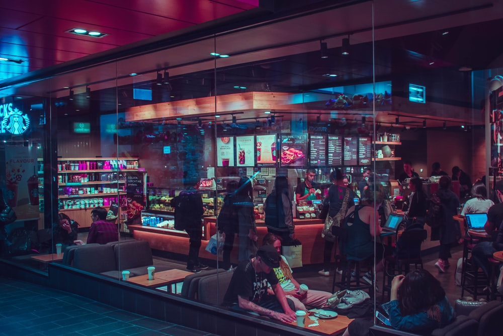 people walking and sitting inside cafe during nighttime