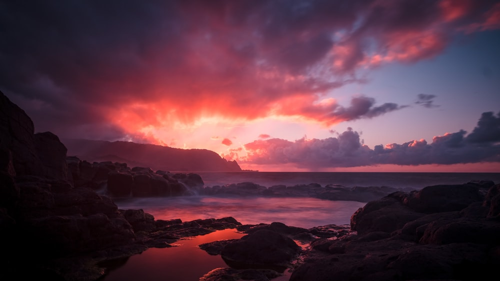 landscape photo of body of water in sunset