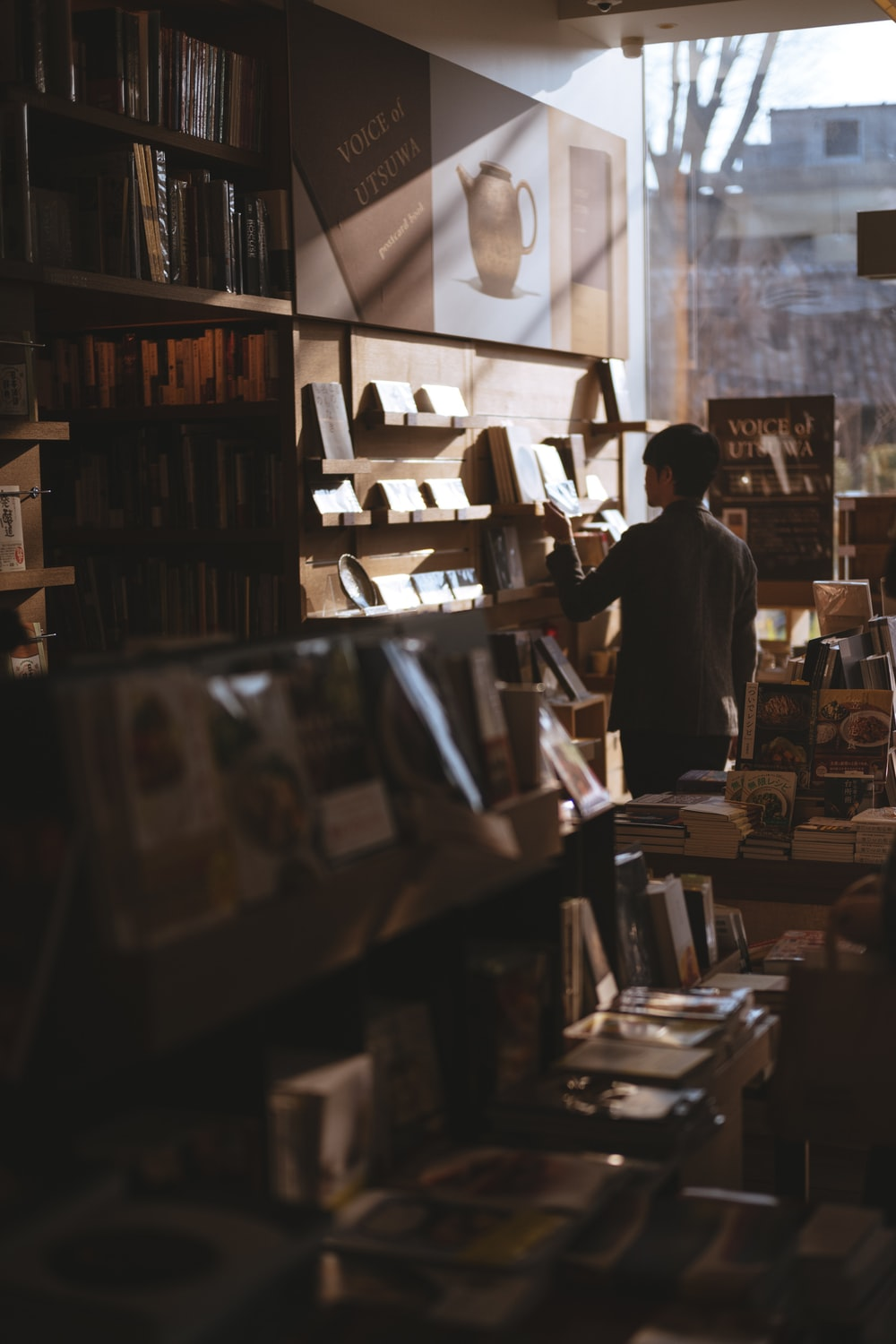 man standing inside library finding books