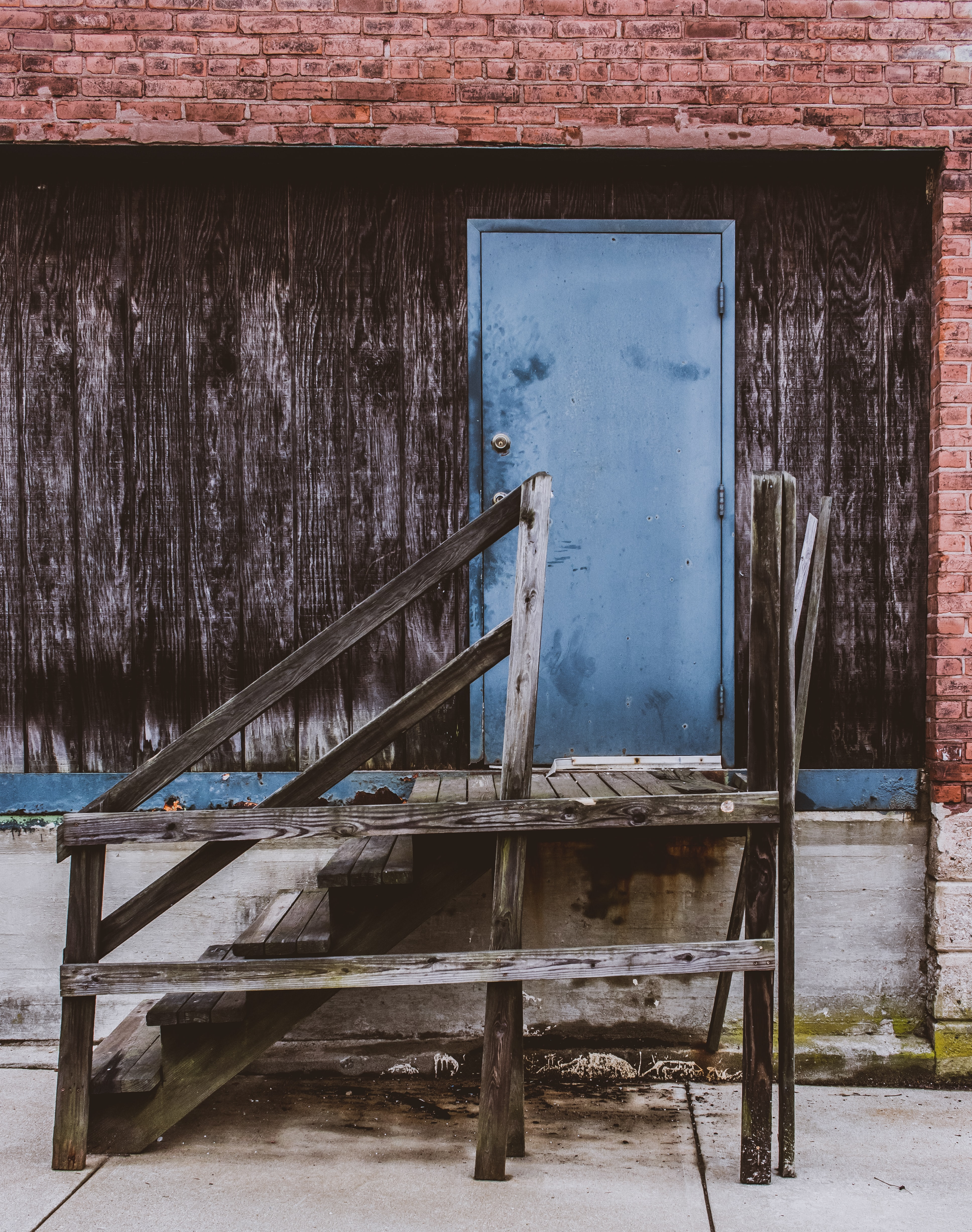 gray wooden stairs and blue door at daytime