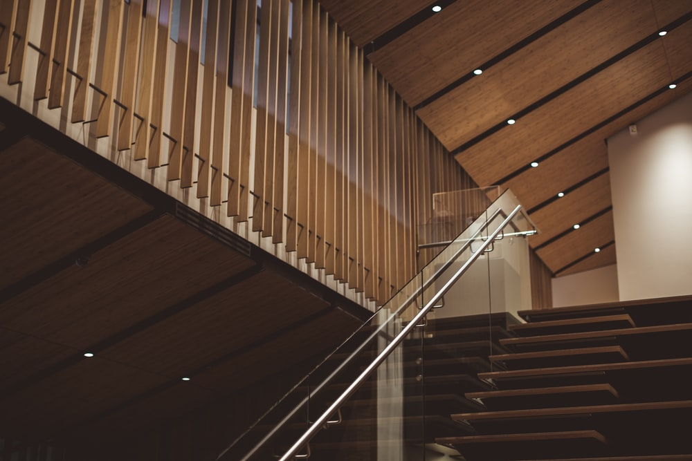 brown wooden stair with glass fence