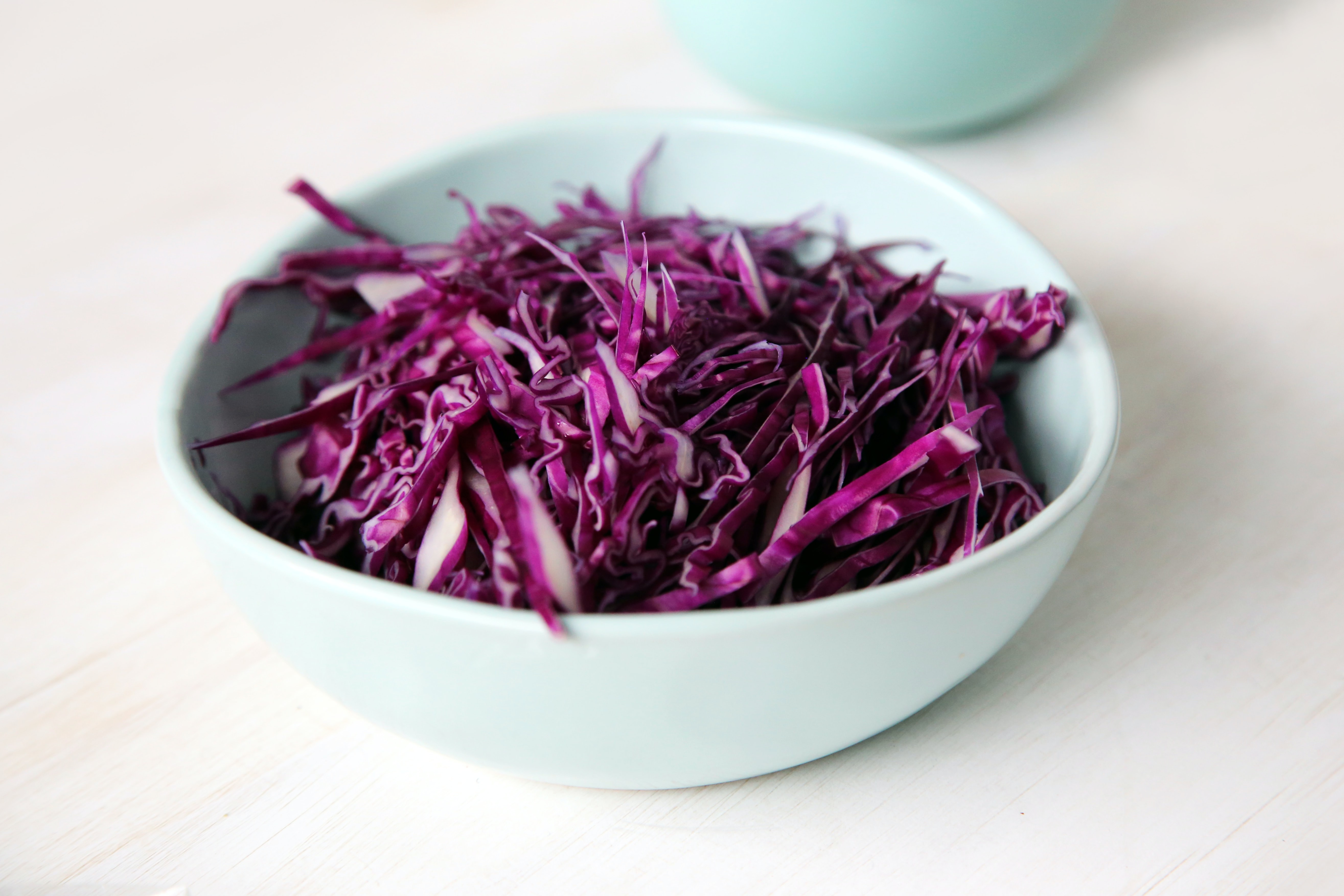 selective focus photography of purple petal filled bowl