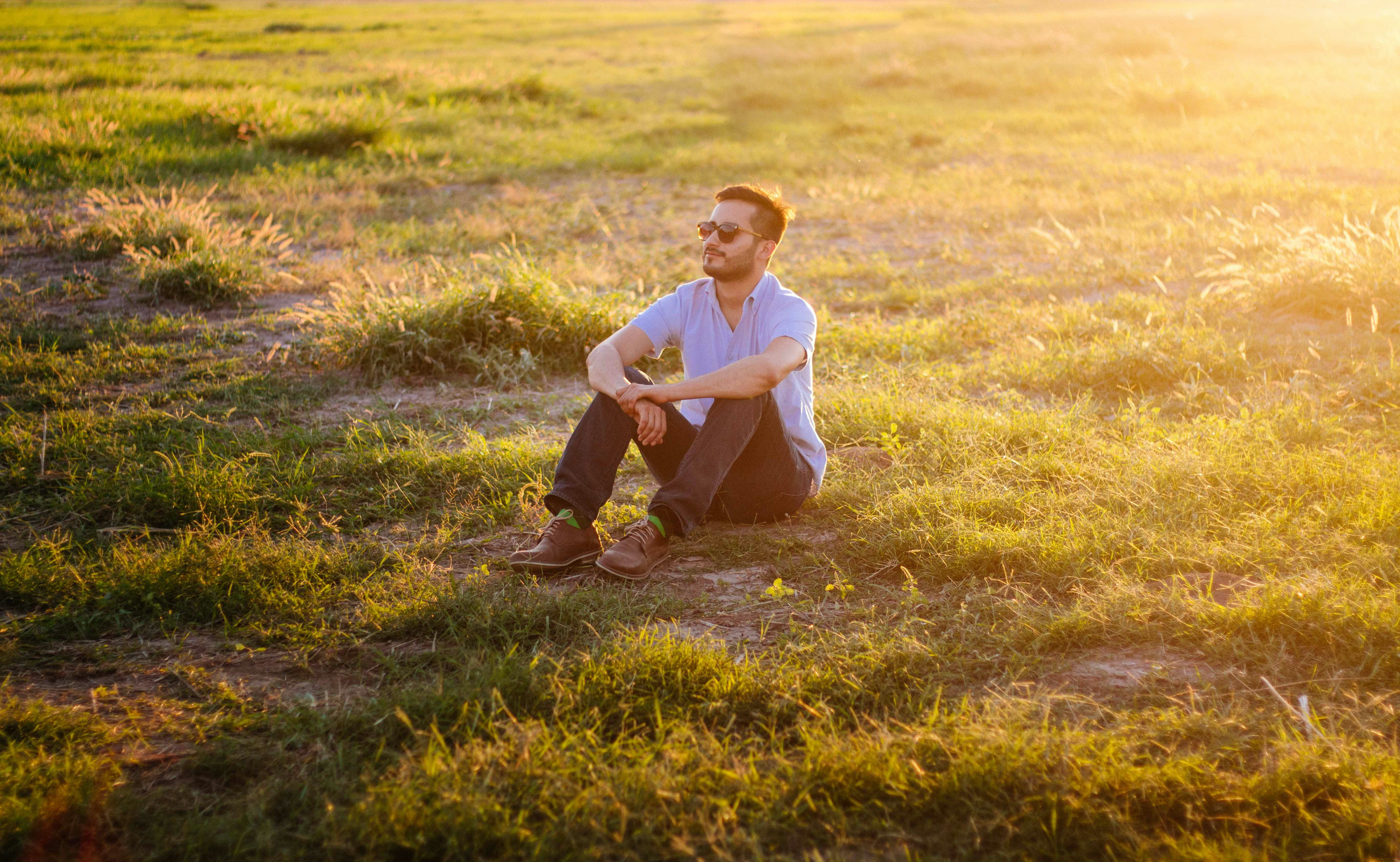 man sitting on green grass field
