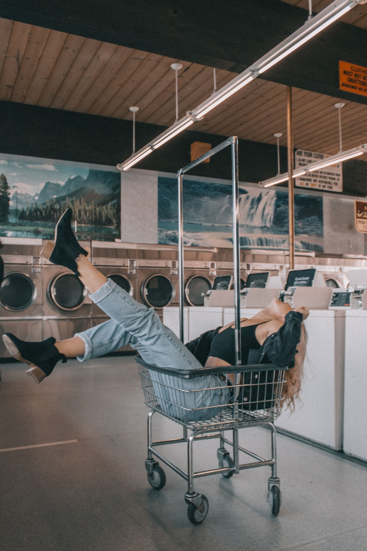 woman in grey metal laundry cart