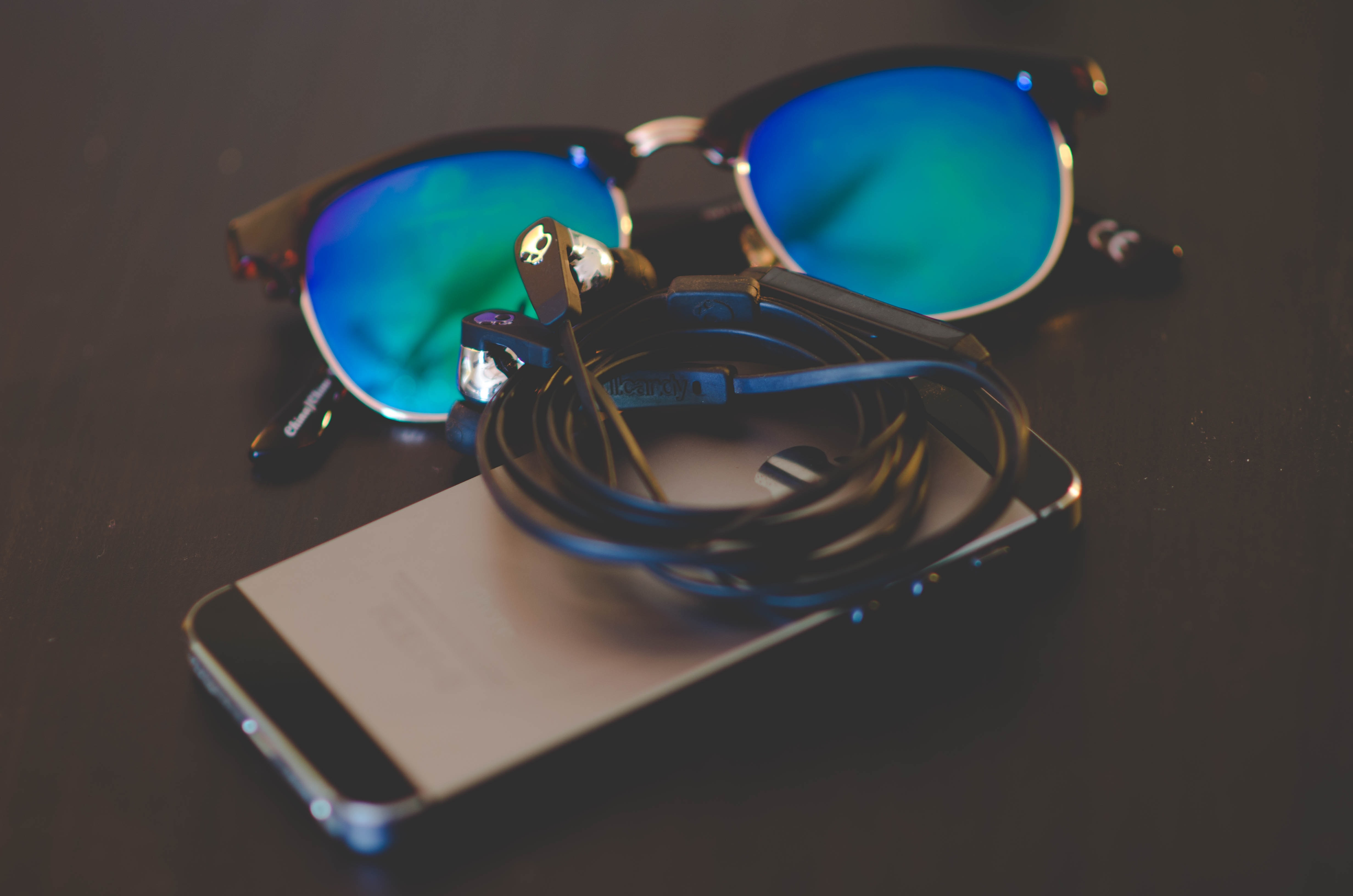 space gray iPhone beside Clubmaster-style sunglasses