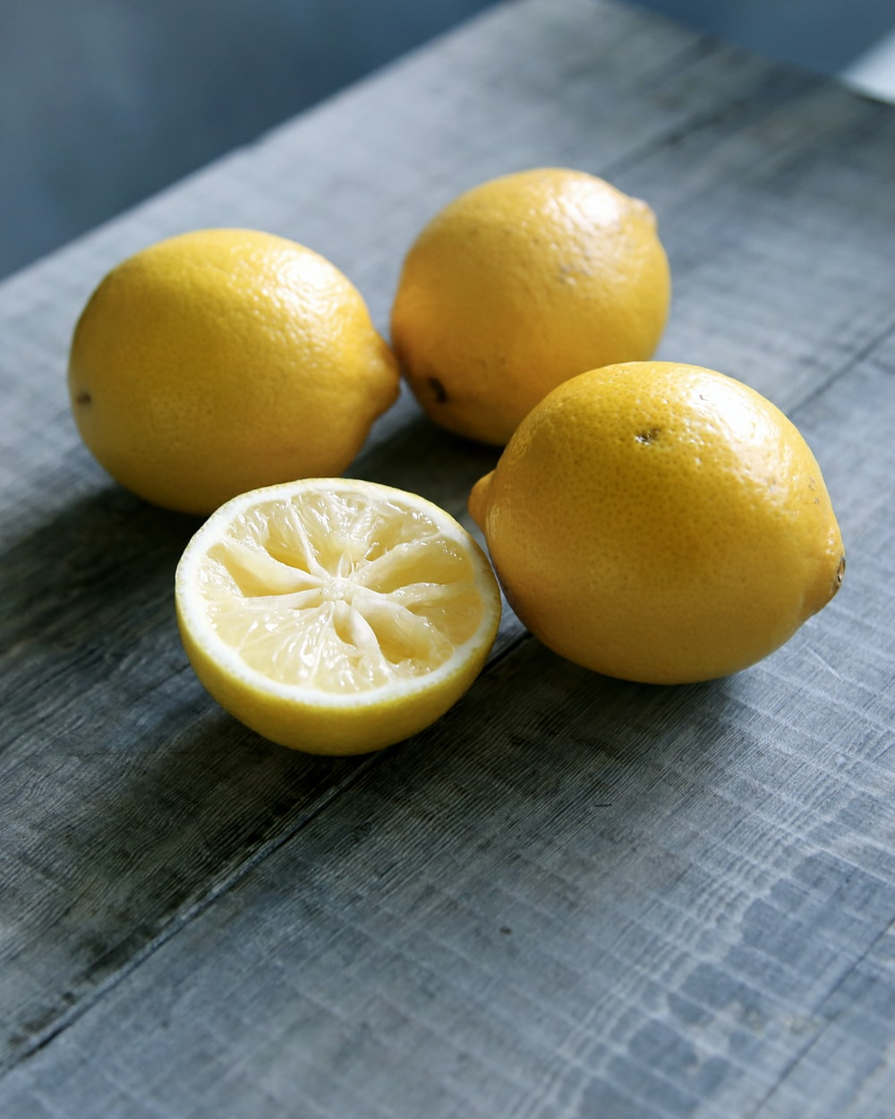 three yellow lemons beside sliced lemon placed on gray wooden surface