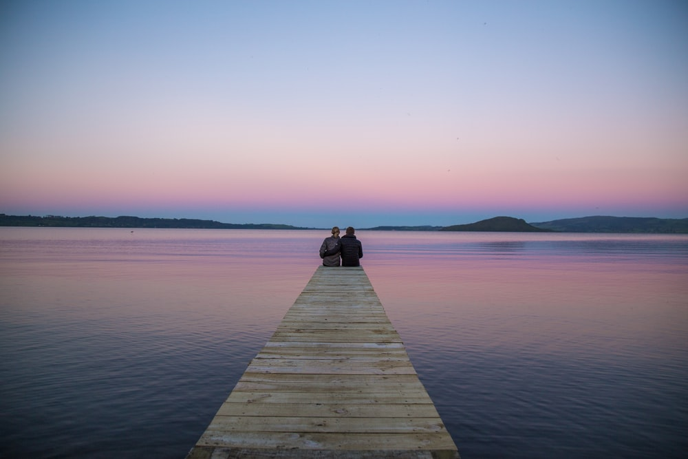 two persons sitting on ocean dock