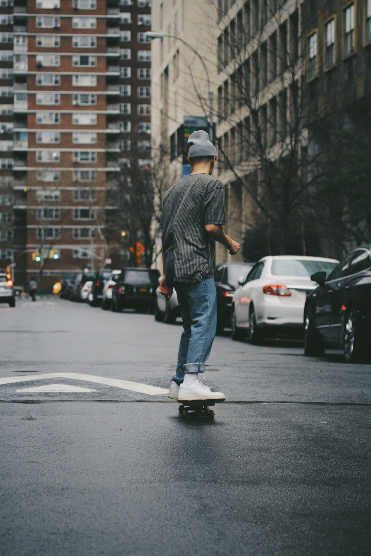 man riding skateboard near high rise building
