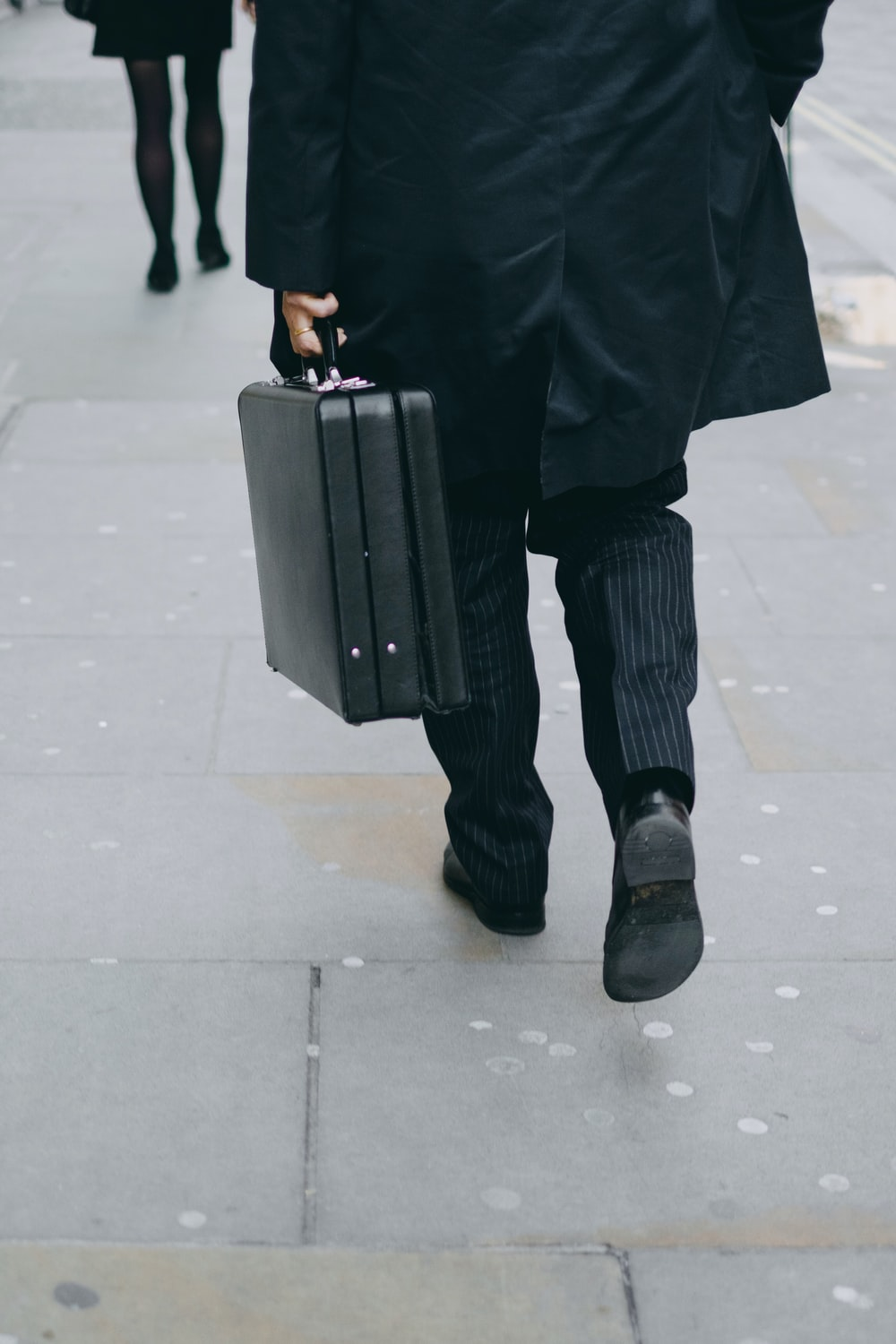 person carrying suit case while walking on pavement