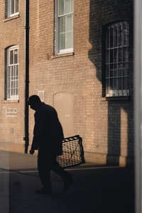 silhouette of man about to walk near building