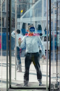 man leaning on glass door