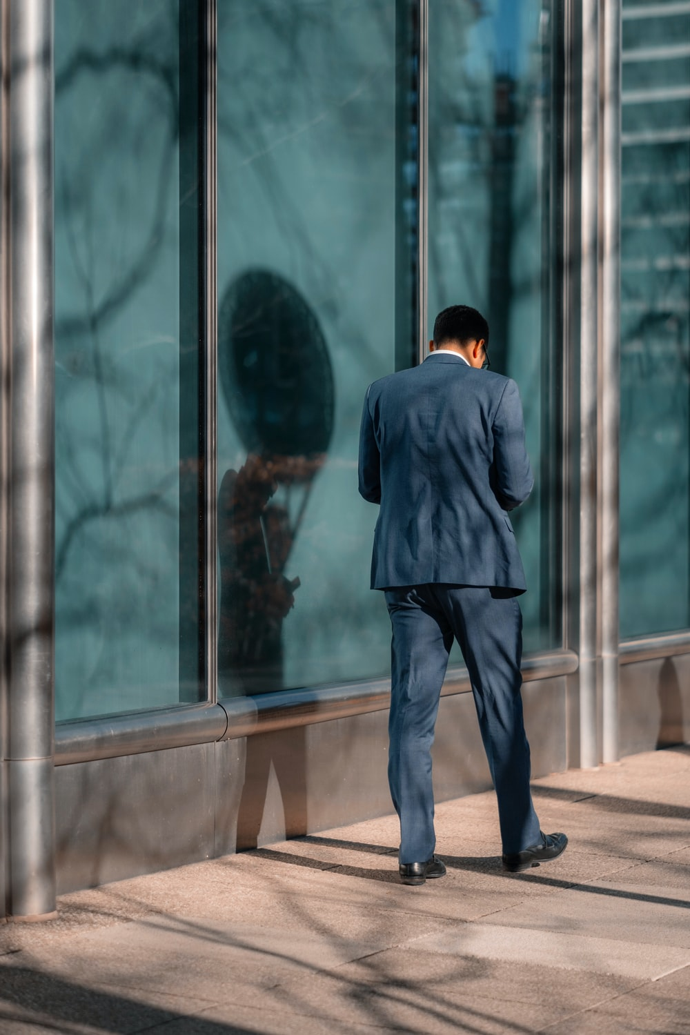 man standing near glass wall