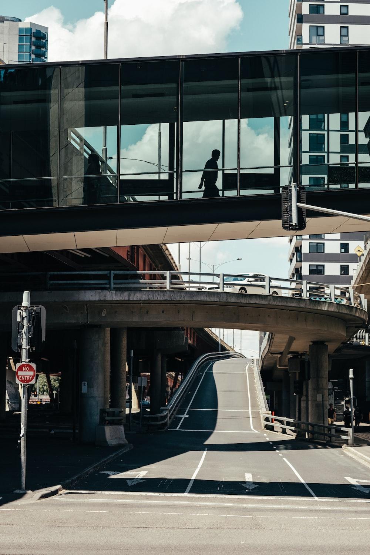 man walking on glass roof bridge near gray concrete road during daytime