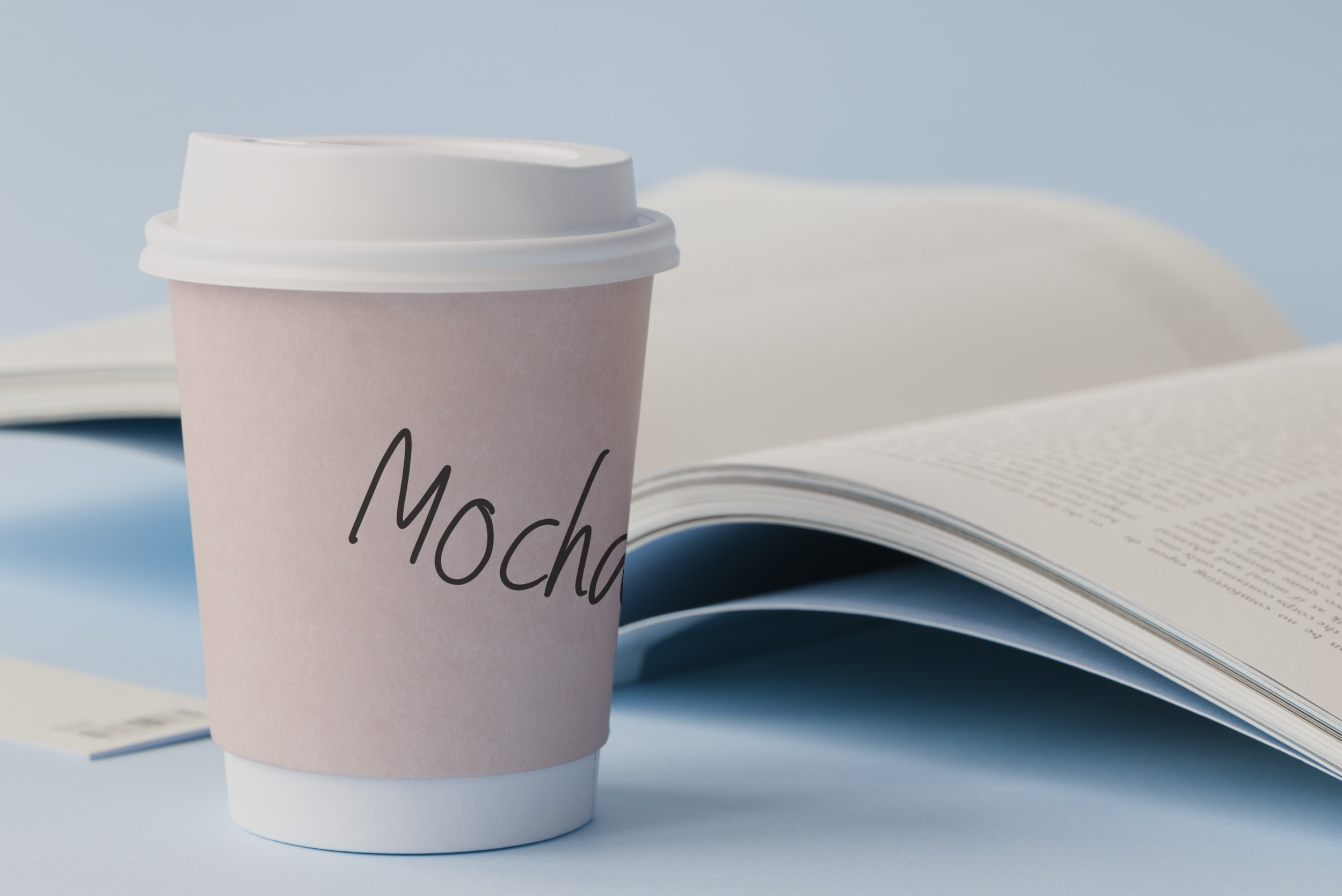 white paper cup on top of white surface beside book
