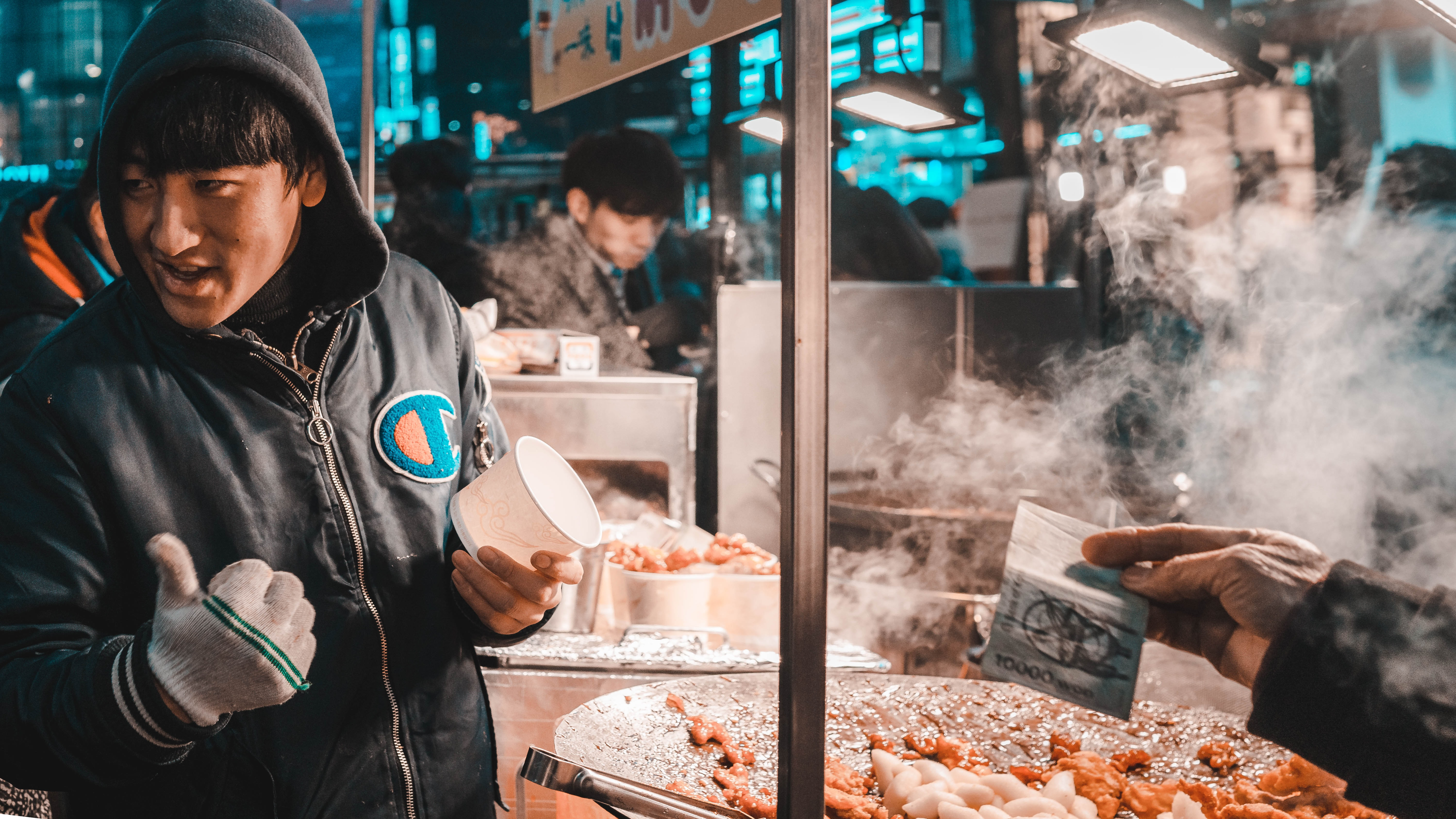 man holding disposable cup standing beside food cart