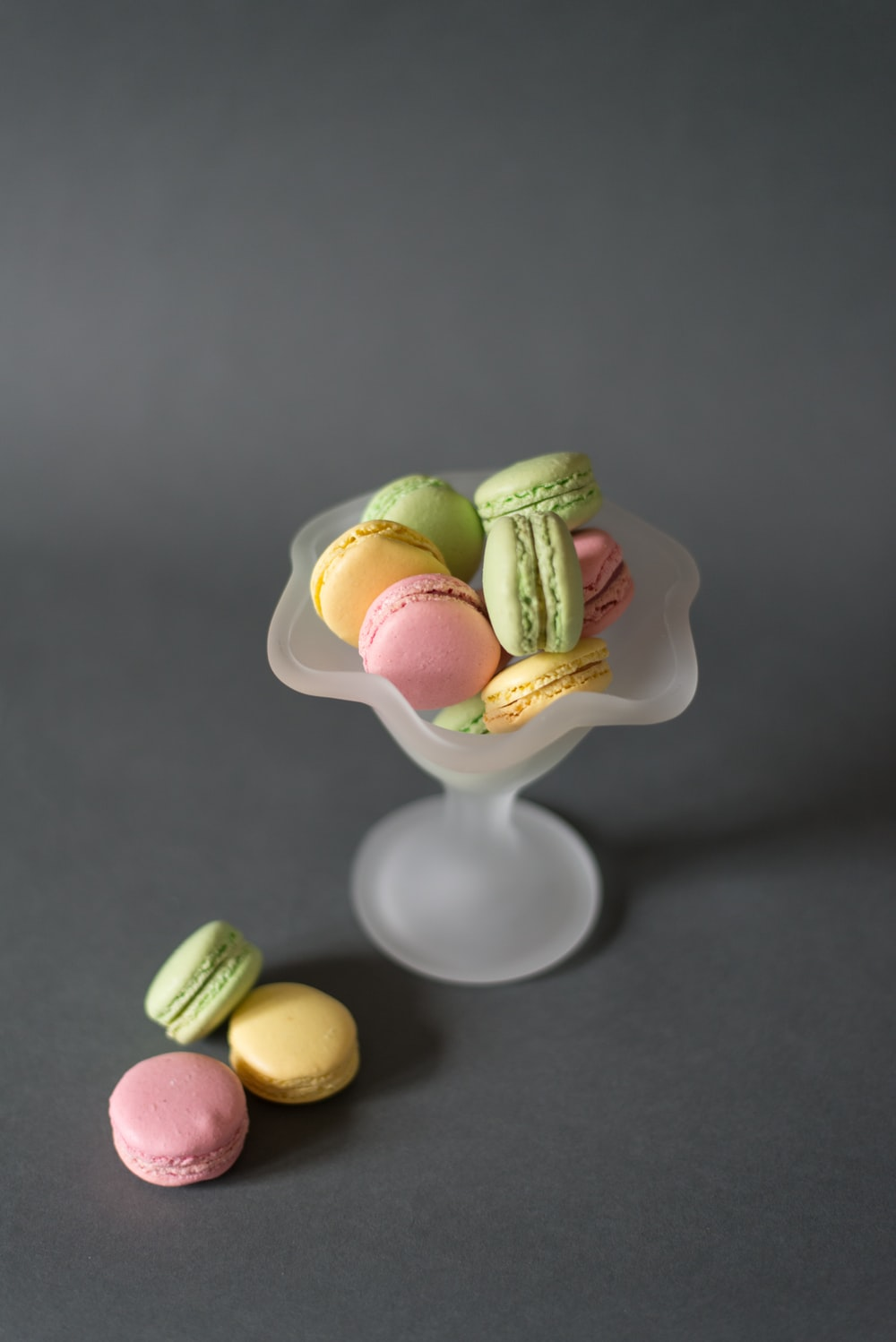 assorted-color macarons on gray footed bowl