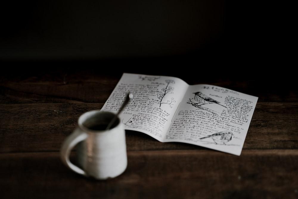 mug near book on wooden surface