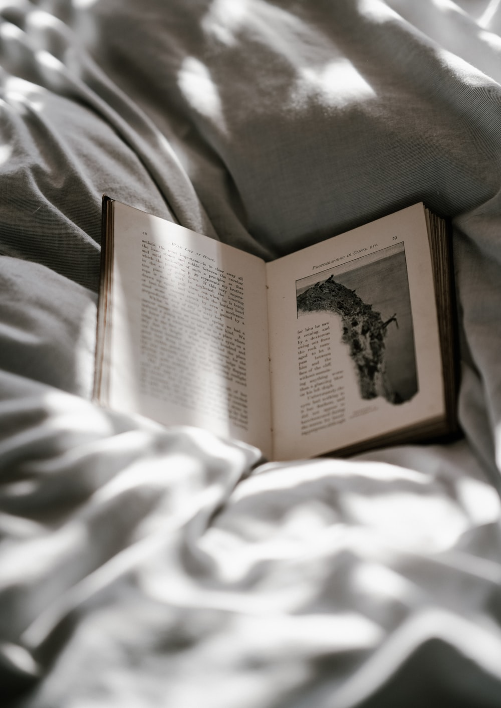 opened-book on top of bed sheet