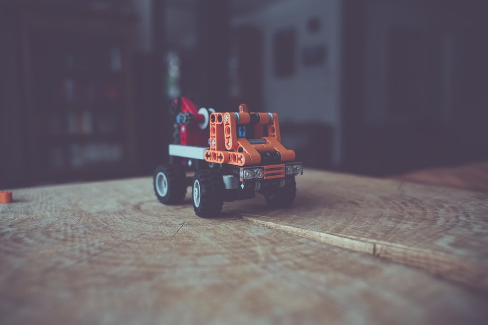 close up photography of lego truck toy on top of brown slab