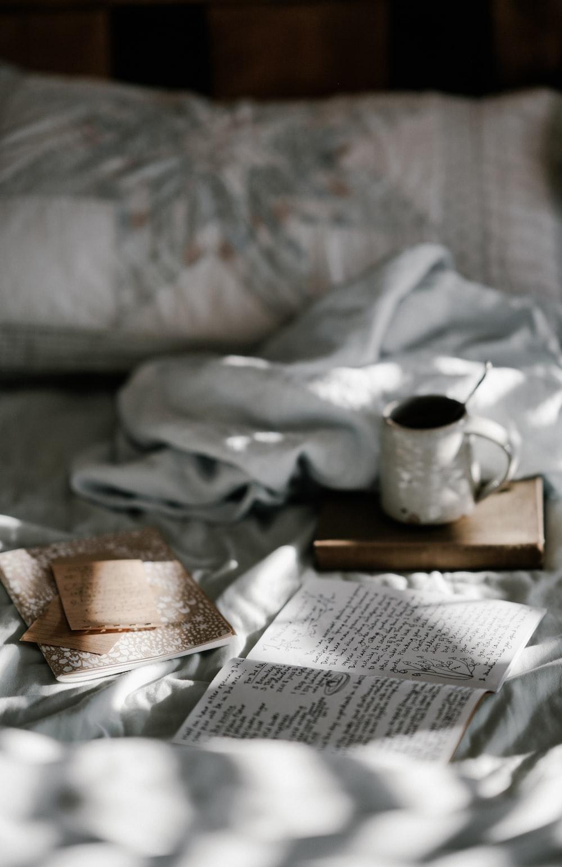 coffee mug on a brown wooden coaster near white blanket