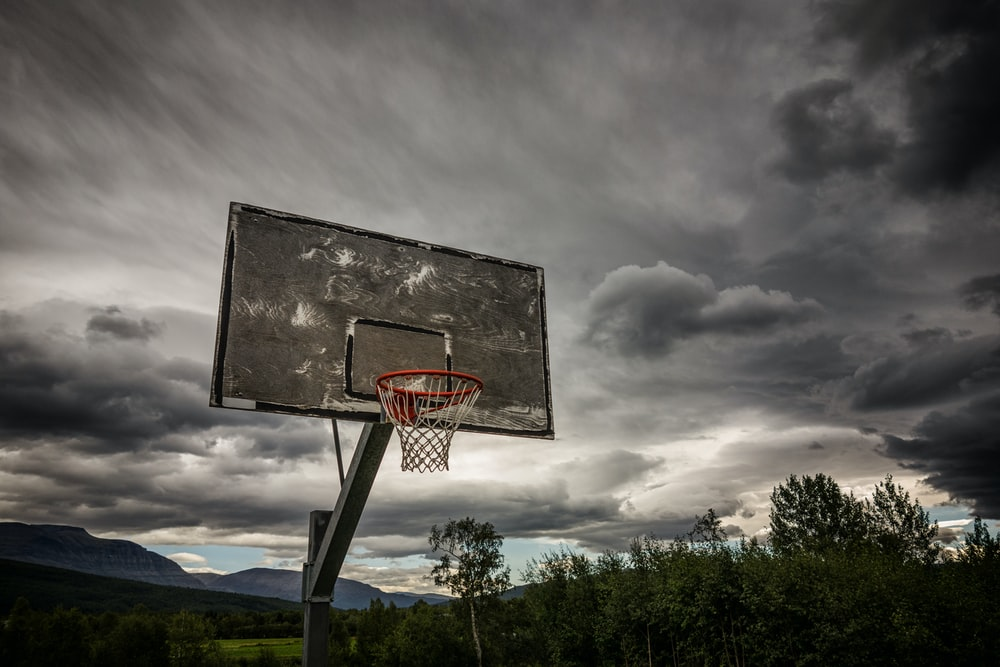 gray and white basketball hoop under dark clouds at daytime