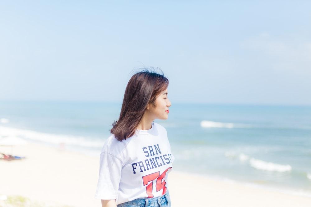 woman in white crew-neck T-shirt walking on seashore