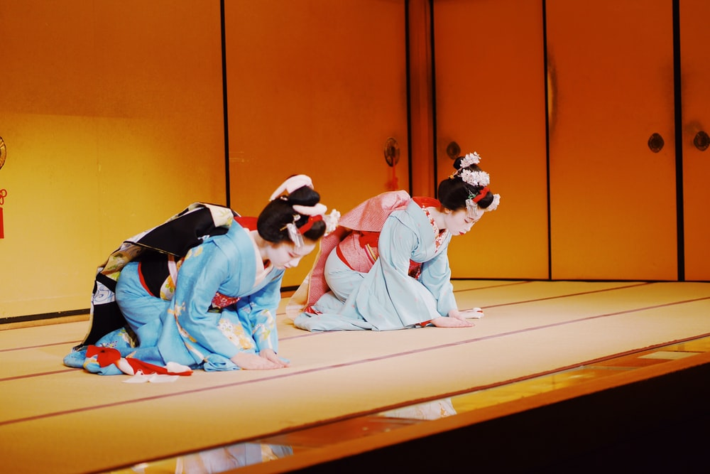 two Geisha on kneeling brown floor