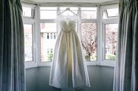women's white sleeveless gown near window