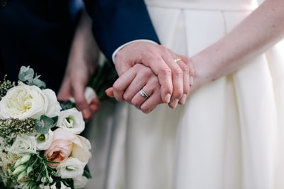 close up photo of man holding woman's hand holding hand zoom background