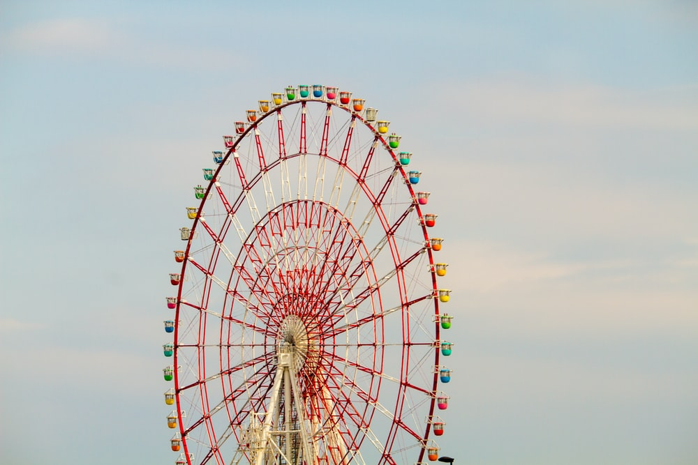 pink and yellow Ferris wheel under clear sky
