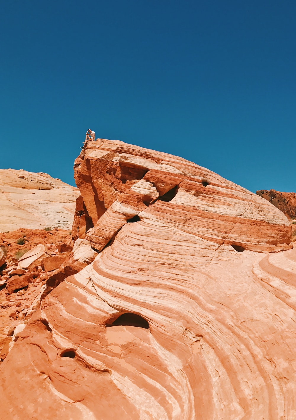 person sitting on top of rock formation