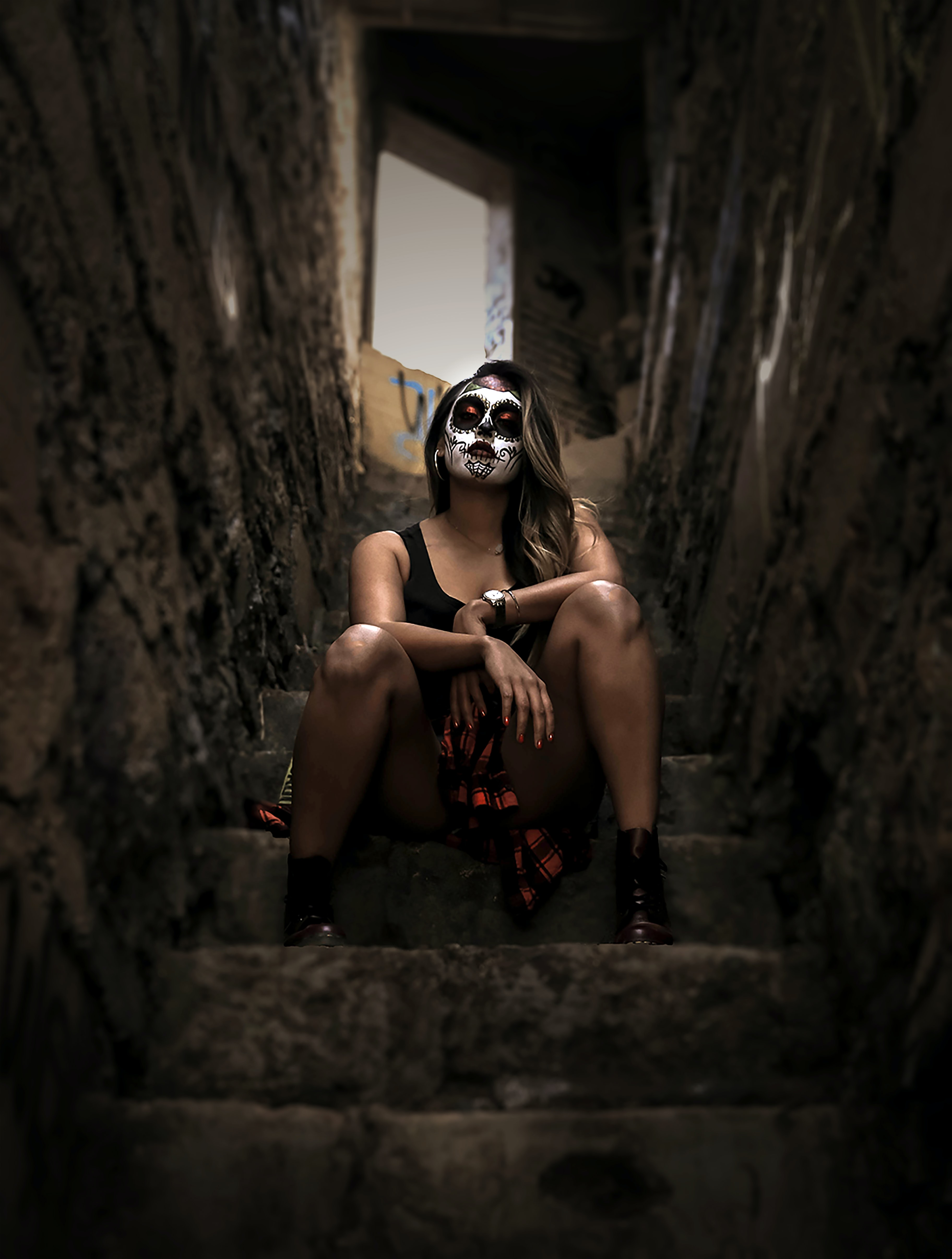 woman wearing skull face paint sitting on stairs