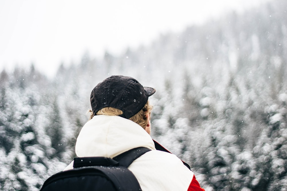 person wearing black cap and backpack bokeh photography