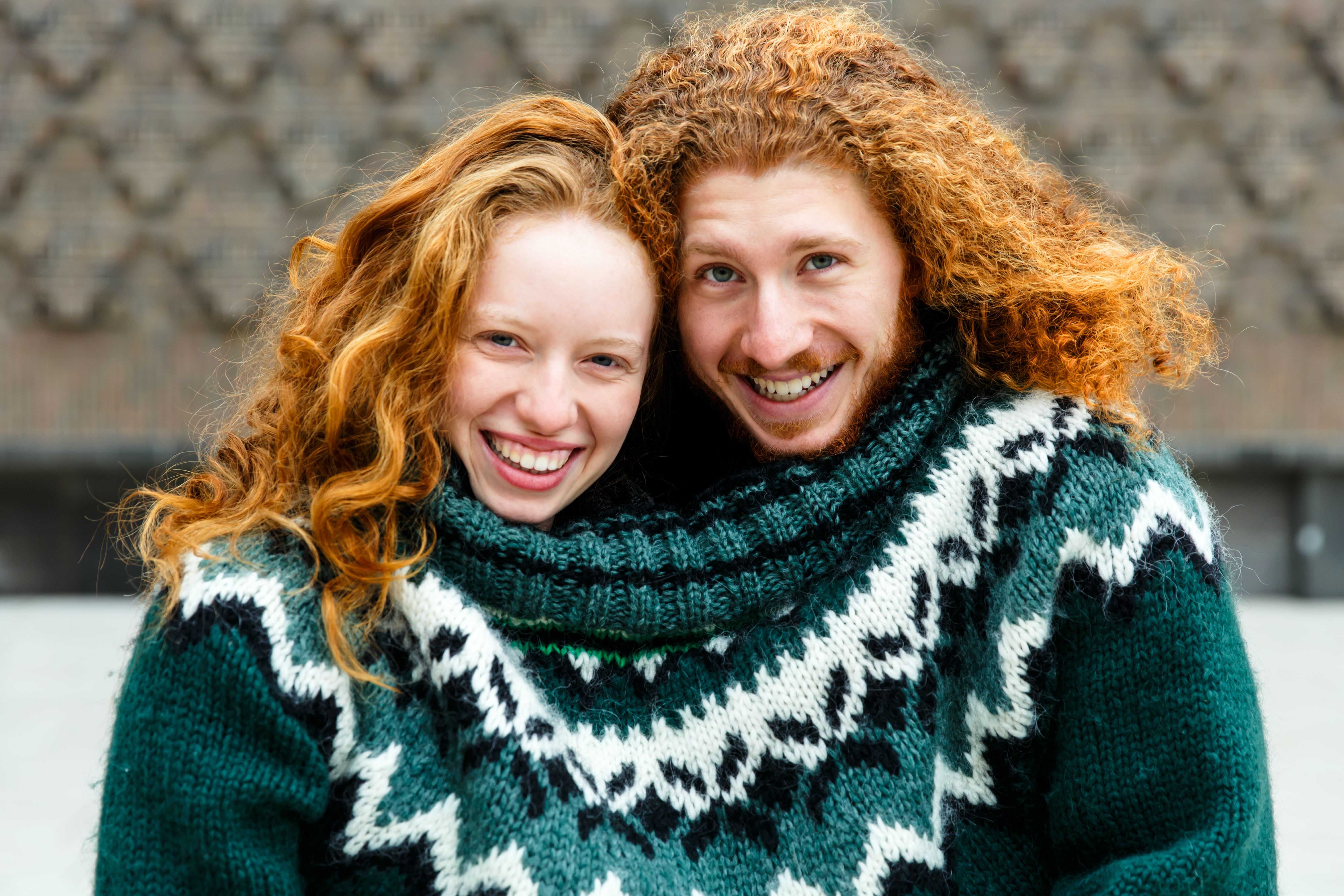 smiling woman and man wearing green knit sweater