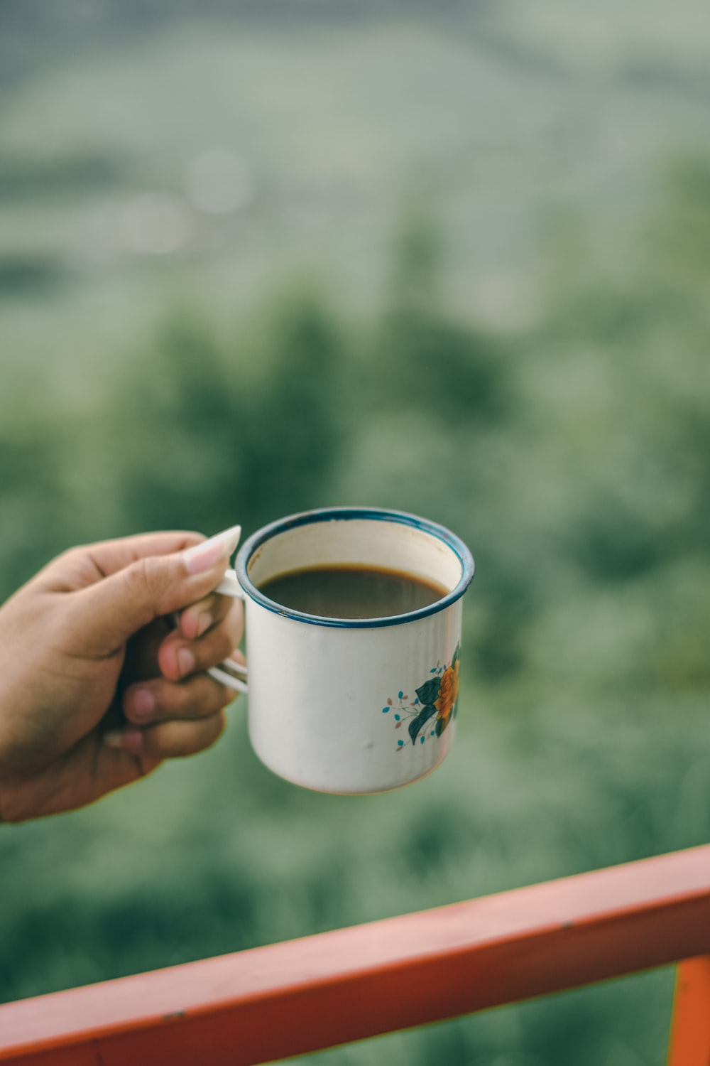 person holding white and orange floral mug
