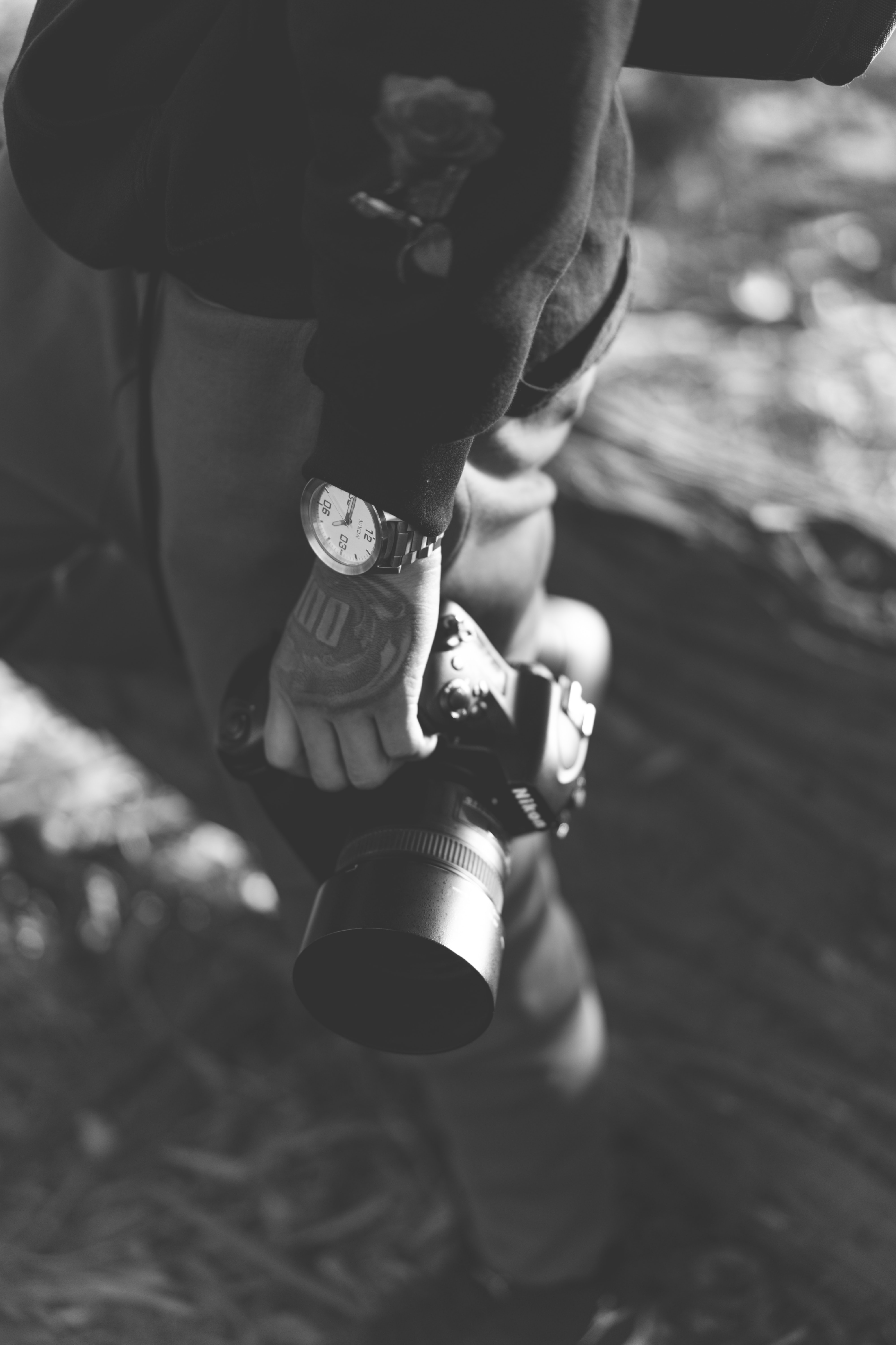 grayscale photo of person holding DSLR camera