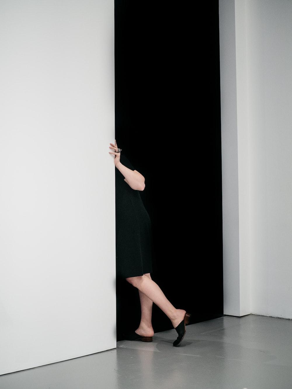 woman standing sneaking on door inside white painted room