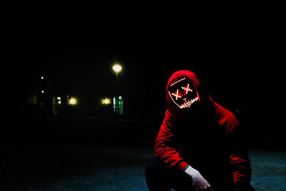 man squatting during nighttime