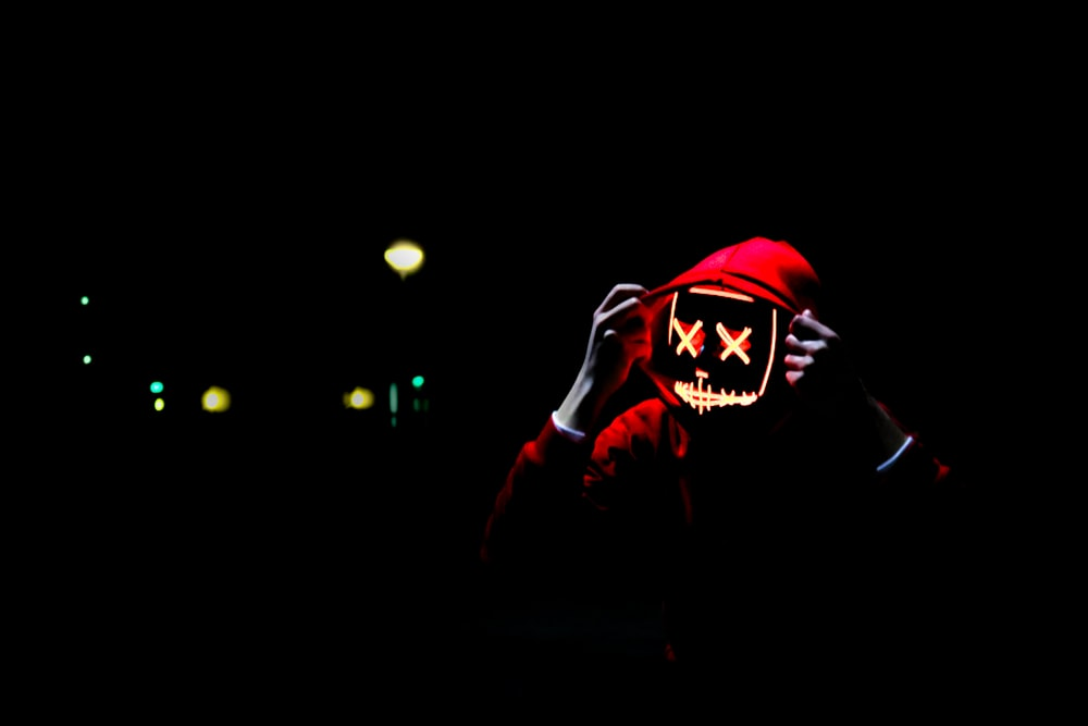 person wearing hoodie and neon mask