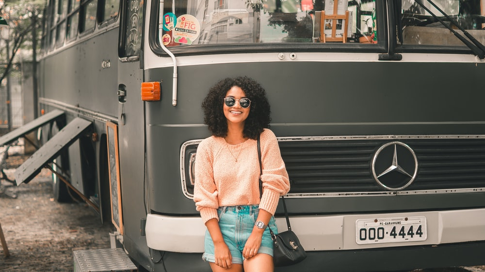 smiling woman standing in front of Mercedes-Benz bus