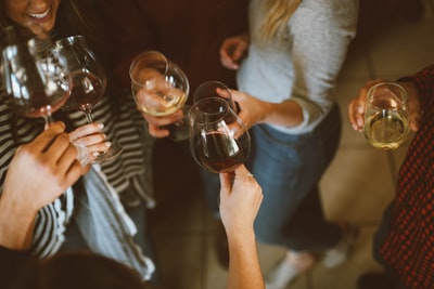 group of people tossing wine glass party teams background