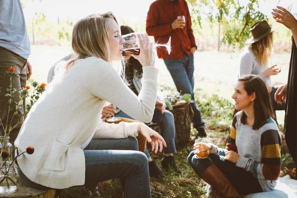 woman sitting near people while drinking