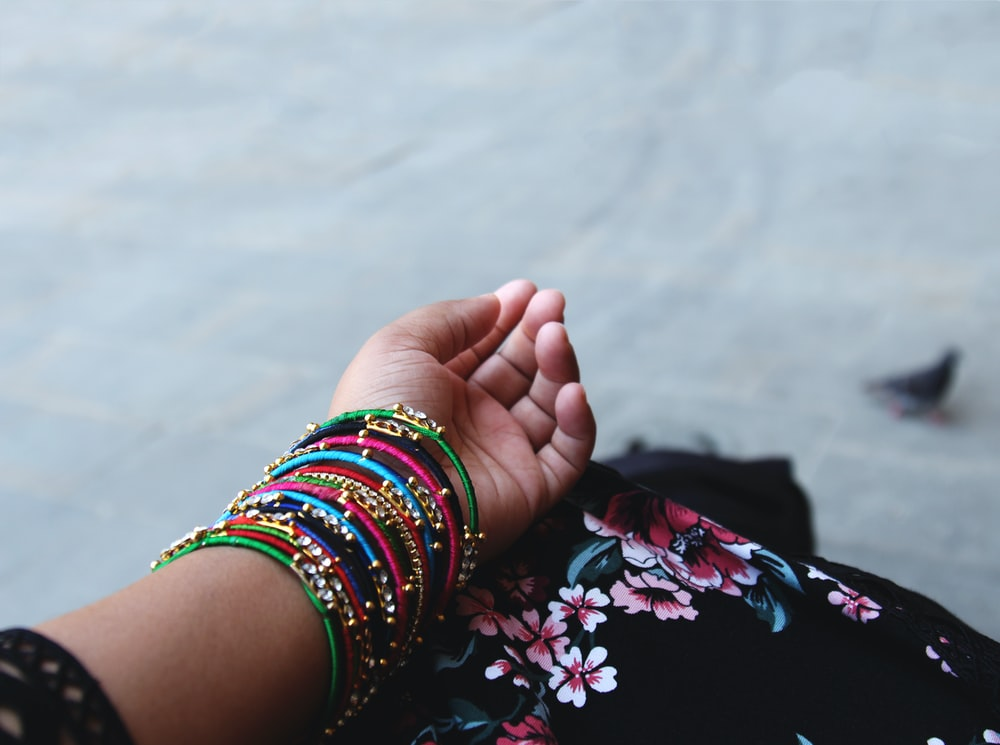 person showing assorted-color thread bangles